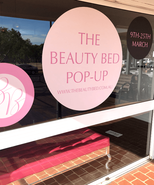 3 separate circles stick in the glass wall of The Beauty Bed shop